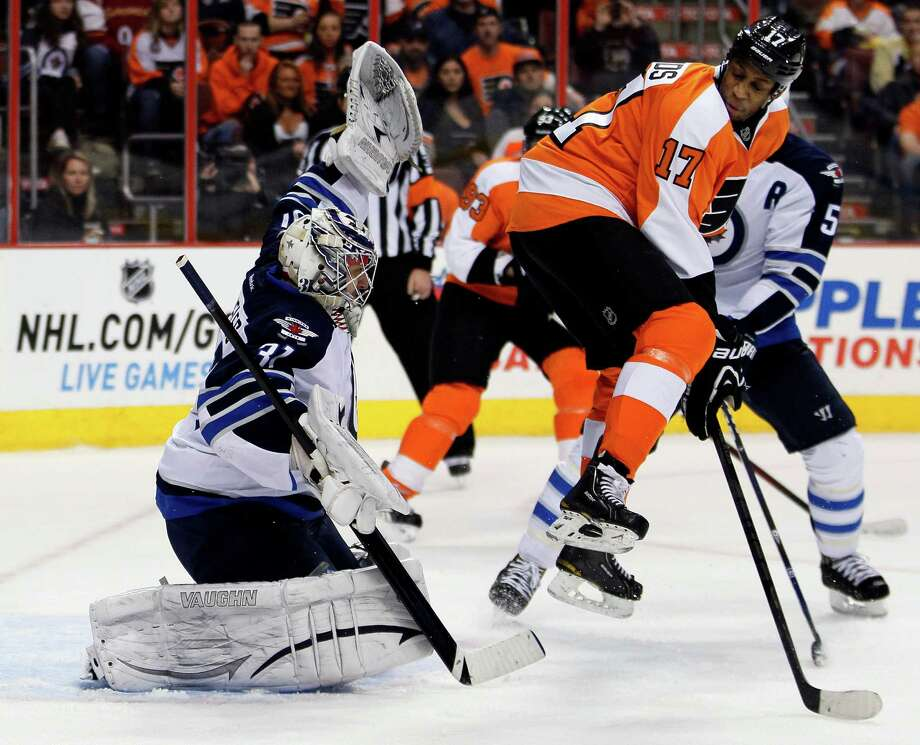 Philadelphia Flyers Wayne Simmonds, right, leaps as the puck shot by Claude Giroux gets past Winnipeg Jets goalie Ondrej Pavelec for a goal in the second period of an NHL hockey game, Saturday, Feb 23, 2013, in Philadelphia. The Flyers won 5-3. (AP Photo/Tom Mihalek) Photo: Tom Mihalek