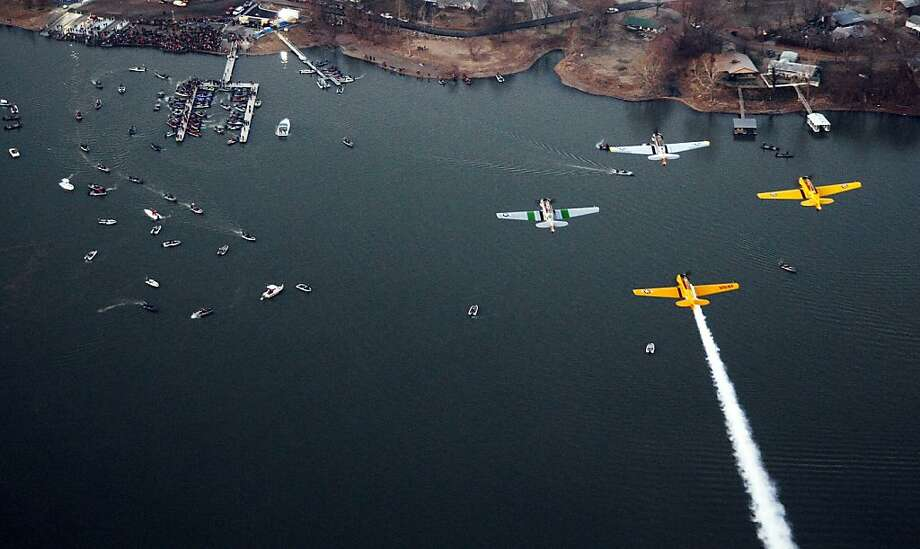 A formation of T-6 aircraft fly over during the playing of the national anthem during the Bassmaster Classic on Grand Lake on Saturday, Feb. 23, 2013, in Tulsa, Okla. (AP Photo/Tulsa World,  Tom Gilbert)  ONLINE OUT; TV OUT; TULSA OUT Photo: Tom Gilbert, Associated Press
