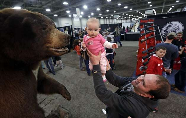 Gun and hunting enthusiast Justin Larsen holds his daughter Avery up to see a bear at the Western Hunting and Conservation Expo Saturday, Feb. 23, 2013, in Salt Lake City. (AP Photo/Rick Bowmer) Photo: Rick Bowmer, Associated Press