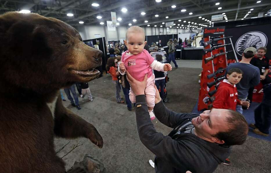 Gun and hunting enthusiast Justin Larsen holds his daughter Avery up to see a bear at the Western Hu