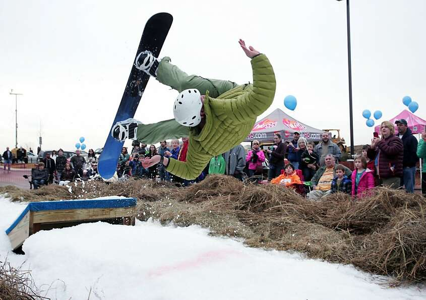 Joe Brogdon attempts a back flip on the snow board jump at Rail Jam on Saturday, Feb. 23, 2013, in C