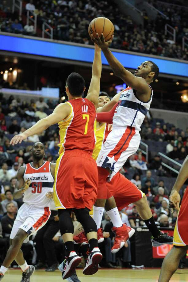 Wizards point guard John Wall, right, had 12 points on 4-for-10 shooting Saturday night. Photo: Mitchell Layton, STR / MCT