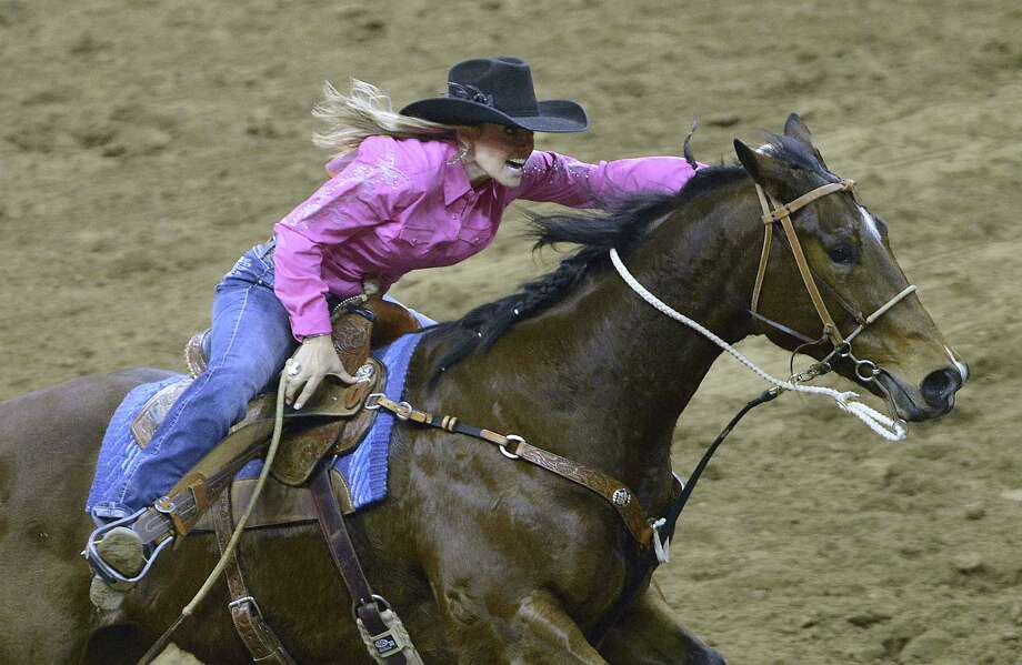 "Shada Brazile and her horse run to victory in the barrel racing competition at the San Antonio Stock Show & Rodeo. ""I was in shock,"" she says after shading runner-up Syndi Blanchard by one-tenth of a second in the final race. Photo: Photos By Billy Calzada / San Antonio Express-News"