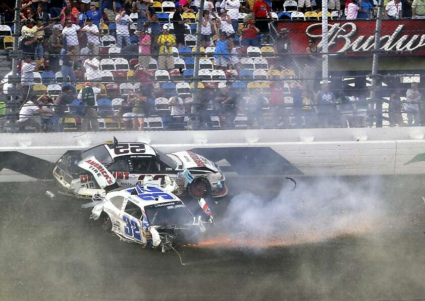 Brad Keselowski (22) and Kyle Larson (32) slide down the front stretch after they were involved in a