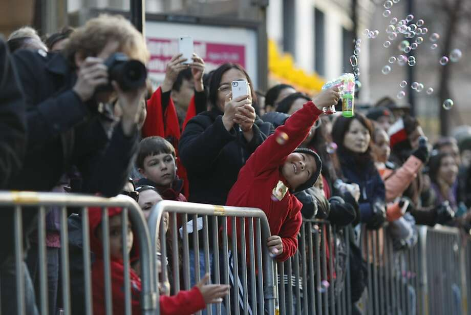 Seven-year-old Lukyind Ladino blows bubbles as the Chinese New Year Parade makes its way down Market St. on Saturday, Feb. 22. The parade is one of the biggest in the country. Photo: James Tensuan, The Chronicle