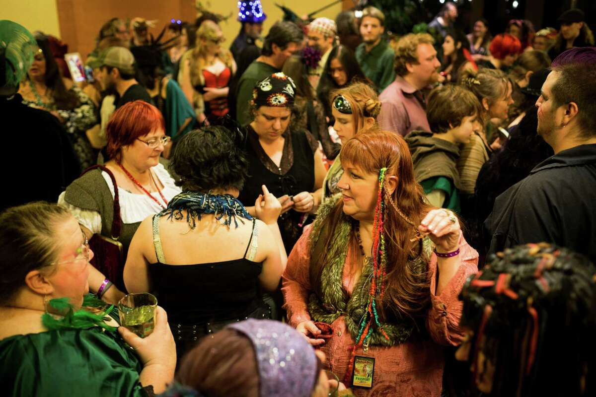 Crowds of costume-clad attendees pose for pictures and compare articles of clothing during FaerieCon West Saturday, Feb. 23, 2013, in Seattle, Wash.