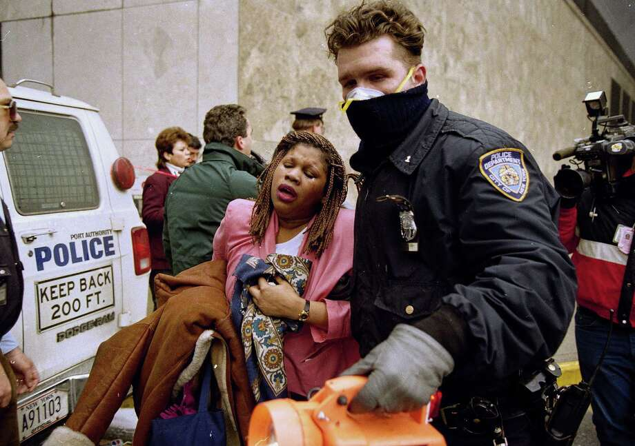 FILE -  In this file photo of Feb. 26, 1993, a New York City police officer leads a woman to safety following a  bomb blast at the World Trade Center. Twenty years ago next week, a group of terrorists blew up explosives in an underground parking garage under one of the towers, killing six people and ushering in an era of terrorism on American soil. (AP Photo/Alex Brandon, File) Photo: Alex Brandon
