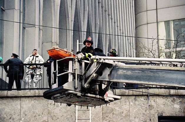 FILE - In this file photo of Feb. 26, 1993, firefighters in a cherry picker remove an explosion victim on a gurney outside one of the World Trade Center's twin towers in New York, after an explosion rocked the complex. Twenty years ago next week, a group of terrorists blew up explosives in an underground parking garage under one of the towers, killing six people and ushering in an era of terrorism on American soil. (AP Photo/Alex Brandon, File) Photo: Alex Brandon