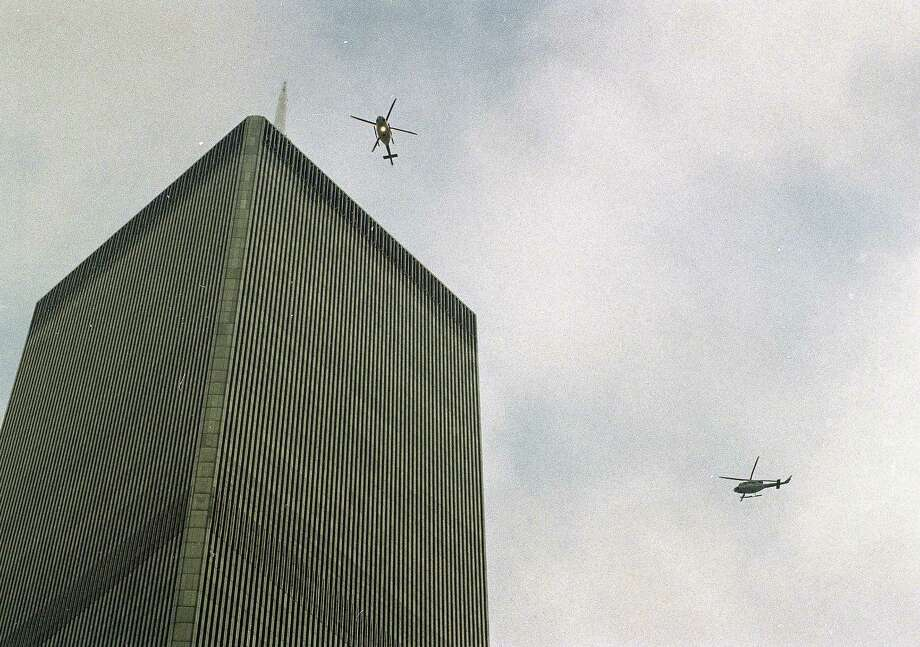 In this file photo of Feb. 26, 1993, helicopters jockey for position over the World Trade Center in New York following a noontime blast, which rocked the twin towers complex. Twenty years ago next week, a group of terrorists blew up explosives in an underground parking garage under one of the towers, killing six people and ushering in an era of terrorism on American soil. (AP Photo/Ron Frehm, File) Photo: Ron Frehm