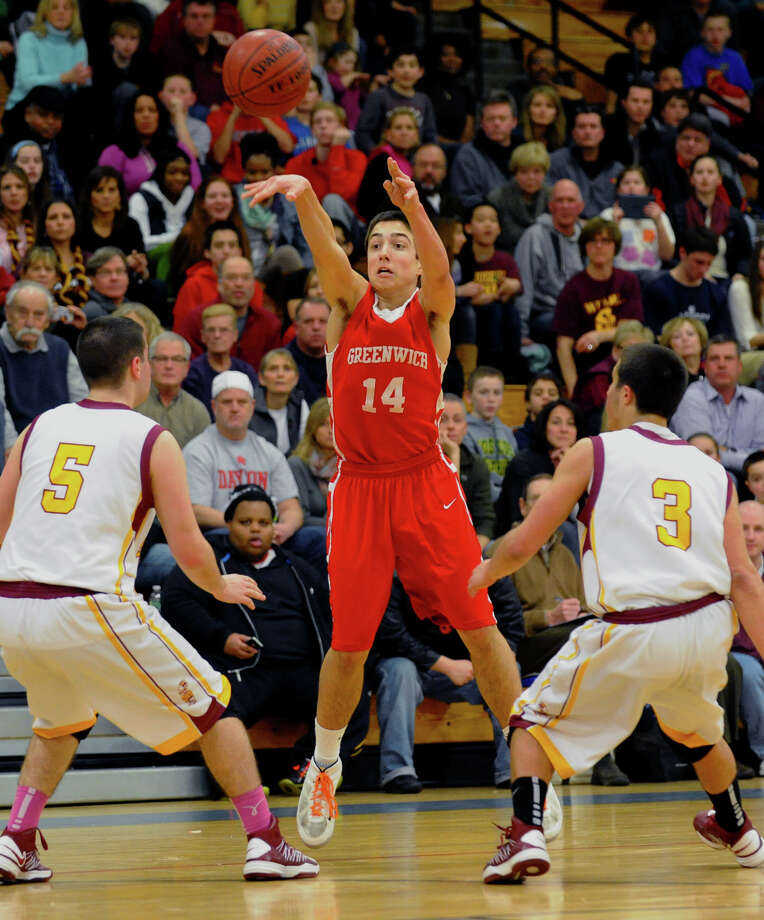 Greenwich's #14 Thomas Baietto passes the ball to a teammate over St. Joseph's #5 Jonathan Dzurenda, left, and #3 Jake Pelletier, during FCIAC boys basketball quarterfinal action in Fairfield, Conn. on Saturday February 23, 2013. Photo: Christian Abraham / Connecticut Post