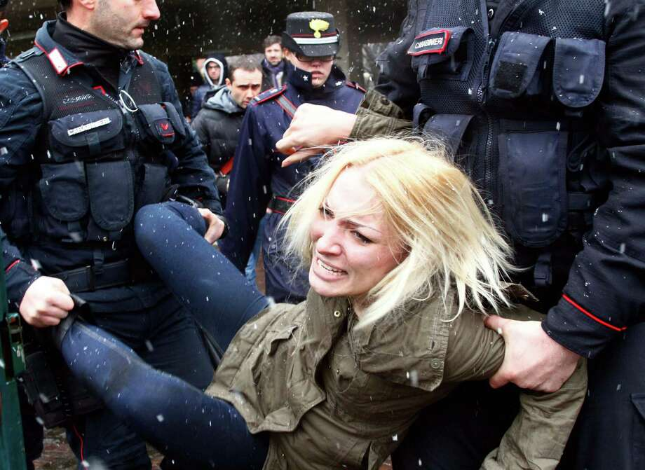 "Police take away a woman protesting where former Italian Premier Silvio Berlusconi was voting, in Milan, Italy, Sunday.  When Berlusconi showed up at a Milan polling place to cast his ballot, three women pulled off their sweaters to bare their breasts and display the slogan ""Basta Silvio!"" (Enough of Silvio) scrawled on their flesh. A cordon of police, already in place for security before the former premier's arrival, blocked Berlusconi's direct view of the women. Police detained the women for questioning. Italian news reports said the three were members of the Femen protest group. Italy votes in a watershed parliamentary election Sunday and Monday that could shape the future of one of Europe's biggest economies. (AP Photo/Spada, Lapresse) ITALY OUT Photo: AP"