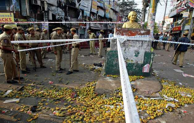 Indian policemen stand guard as oranges are scattered next to a bust of former Indian Prime Minister Indira Gandhi, at the site of one of the two bomb blasts, in Hyderabad, India, Friday. Indian police are investigating whether a shadowy Islamic militant group was responsible for a dual bomb attack that killed over a dozen people outside a movie theater and a bus station in the southern city of Hyderabad, a police official said Friday. Photo: AP