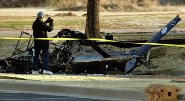 Investigators with the FAA look over the wreckage of a medical helicopter which crashed Friday in front of the Saint Ann Retirement Center in Oklahoma City, Okla. Two people were killed in the crash and a third person was injured.  (AP Photo/The Oklahoman,Paul Hellstern) Photo: AP