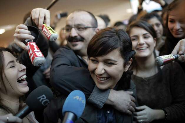 "French-Turkish university student Sevil Sevimli, center, is welcomed by her father, behind left, and relatives, upon her arrival from Turkey at Saint-Exupery airport in Lyon, central France, Wednesday. A court in Turkey on Friday sentenced the French-Turkish student to more than five-years in prison for ""terrorist propaganda"" but allowed her to return to France pending an appeal, her lawyer said. Arrested after joining a May Day parade in Istanbul, she went on trial in September on charges that risked up to 32 years in prison. Photo: AP"