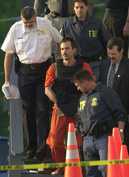 Eric Robert Rudolph, shown center in 2003, is escorted from the sheriff's department in Murphy, N.C.