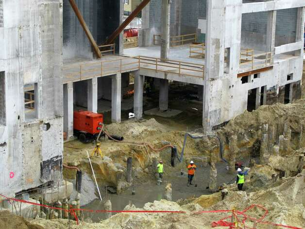 Workers labor on the Gaillard Center in  Charleston, S.C., on Friday. Across the building site, a previously unknown graveyard was found this month. The graves were found as workers dug foundations for a $142-million performing arts center and exhibition hall. Photo: AP