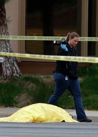 An investigator walks past the tarp covered body of a shooter in Orange, Calif., Tuesday. Police say a chaotic 25-minute shooting spree through Orange County left a trail of dead and injured victims before the shooter killed himself. Orange County sheriff's spokesman Jim Amormino say there are at least six crime scenes with three people, including the suspected gunman, dead and several others wounded. Tustin police Supervisor Dave Kanoti said the shootings started with an apparent carjacking just after 5 a.m. Tuesday in an unincorporated Ladera Ranch area of Orange County. Photo: AP