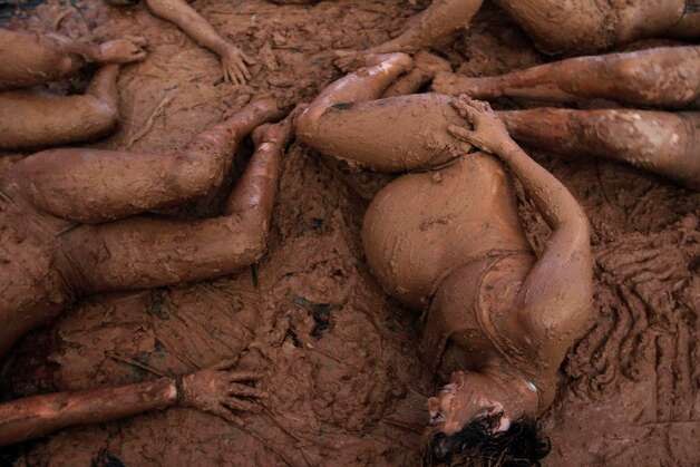 Women bathe in mud during a presentation during the inauguration of the National Meeting of Rural Women, in Brasilia, Brazil, on Monday. The four-day event aims to discuss the issues of violence against women and exploitation of women in rural areas. Photo: AP