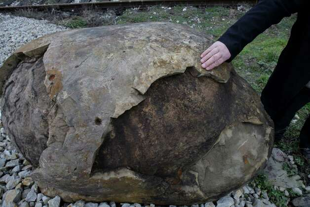 "Bosnian man Dimitrije Tatic, shows  the rusty, egg-shaped rock and cracks on its surface in the village of Kostajnica 200 kms north of Sarajevo, on Saturday, Feb. 23, 2013. A stone quarry in Bosnia has become a popular draw for the locals in the wake of the meteor explosion over Russia last week. Few years ago, workers in the quarry in Kostajnica dug out a massive, rusty, egg-shaped rock, which everyone there believes is a meteorite because of an old tale passed down from generation to generation in this small central Bosnian town. ""Old people, 104 years old, told us that their elderly told them about a huge rock which fell here from the sky some 200 years ago,"" quarry owner Dimitrije Tatic said. ""They believed that it feel off the moon. It was so hot that it was impossible to approach it and also when it fell all the houses in the vicinity collapsed,"" he added. The rock that is estimated to weigh 7 tons started drawing visitors since a meteor exploded over Russia's Ural Mountains last week leaving nearly 1,200 people injured. Photo: AP"