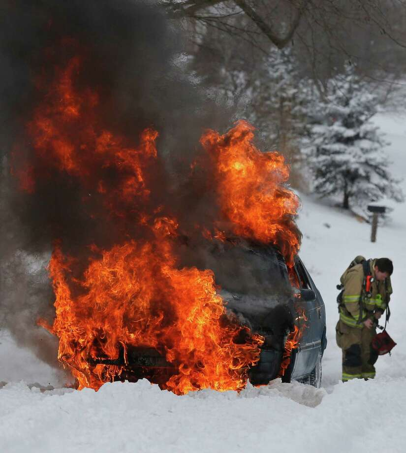 A Lawrence Firefighter prepares to extinguish a vehicle fire in Lawrence, Kan., Thursday. The car caught on fire trying to make it up a snow covered hill on Lawrence Avenue. Photo: AP