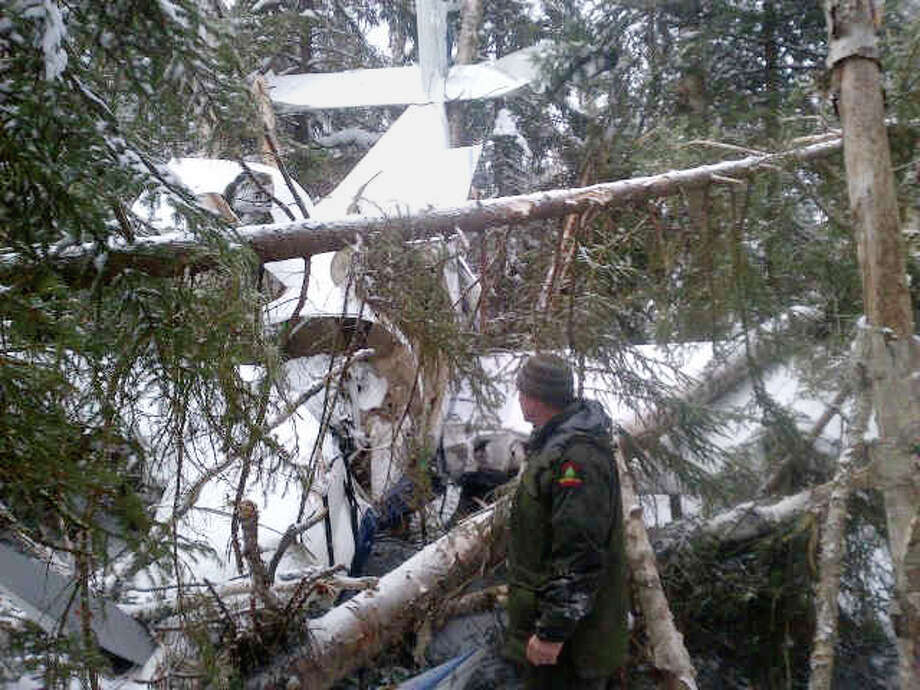In this photo downloaded from the New York Governor Andrew Cuomo's media website, New York Department of Environmental Conservation Forest Ranger Dan Knox examines the wreckage of an experimental aircraft that crashed in the woods just outside the village of Lake Placid, N.Y., Friday. First responders were dispatched to the crash the evening before to rescue three men who were on the aircraft, who were ferried from the woods on snowmobiles. They were checked out by ambulance crews and released after declining further treatment. Photo: AP