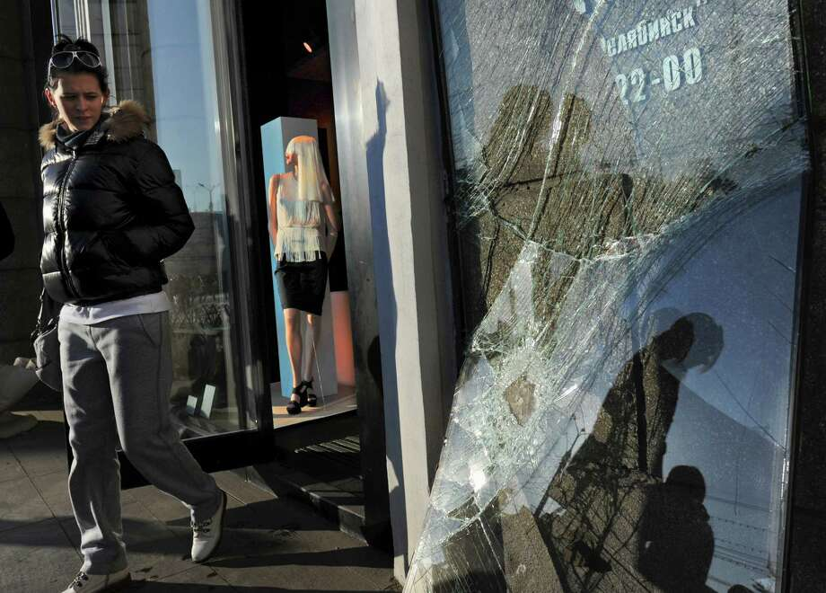 A woman leaves a shop with a broken window in Chelyabinsk, Russia, on Monday  as part of the local damage after a meteorite exploded over the region on Feb. 15.  A total of 53 pieces of space debris have been brought for analysis to the university in Yekaterinburg, with the largest being about one centimeter in diameter, and the smallest is about one millimeter. Photo: AP