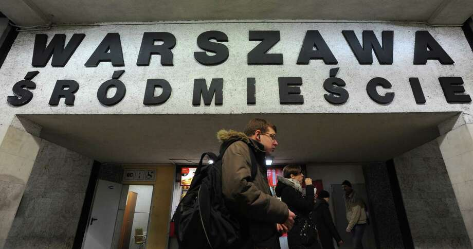 People walk under a board with the name of a train station with several Polish diacritical marks, in Warsaw, Poland, Thursday. Polish language experts have launched a campaign, as part of the UNESCO International Mother Language Day, to preserve the challenging system of its diacritical marks, saying the tails, dots and strokes are becoming obsolete under the pressure of IT and speed. The name of the station reads Warsaw Downtown. Photo: AP