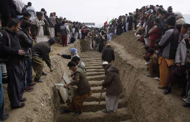 Pakistani Shiite Muslims prepare to bury bombing victims in Quetta, Pakistan on Wednesday. Pakistani Shiites buried their kin killed in a massive bombing last weekend in the southwestern city of Quetta but the funeral on Wednesday was marred by gunfire as both protesters and police fired into the air. Photo: AP