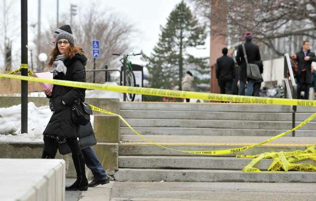Pedestrians walk by police tape on the MIT Campus in Cambridge, Mass.,after police responded to reports of a gunman on campus that Cambridge police later said were unfounded, Saturday. Police said that officers searched for a man reported to be carrying a long rifle and wearing body armor and found nothing. A spokeswoman for the university says the school also called off a campus-wide lockdown. Photo: AP