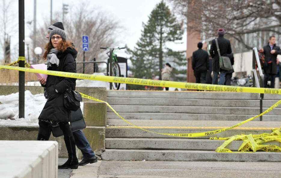 Pedestrians walk by police tape on the MIT Campus in Cambridge, Mass.,after police responded to repo