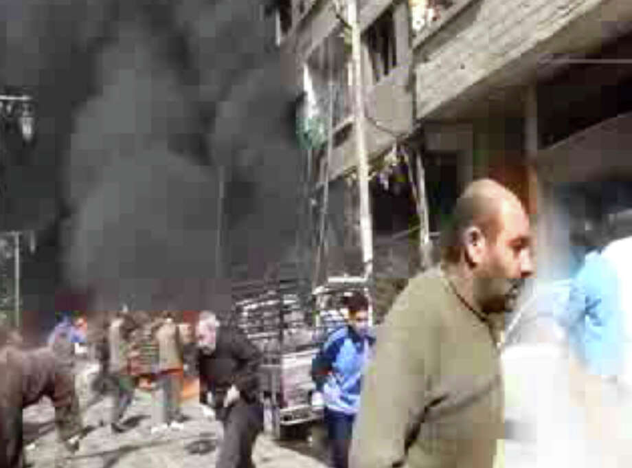 This image taken from video obtained from Ugarit News, which has been authenticated based on its contents and other AP reporting, shows smoke and fire after a fighter jet crashed into a suburb of Damascus, Syria, Wednesday. The United Nations says at least 70,000 people have been killed since the conflict began in March 2011 as an uprising against Bashar Assad's rule. The revolt turned into a civil war that has taken increasingly sectarian overtones with mostly Sunni Muslim opposition forces fighting to topple the regime dominated by Alawites, an offshoot Shiite group. Photo: AP