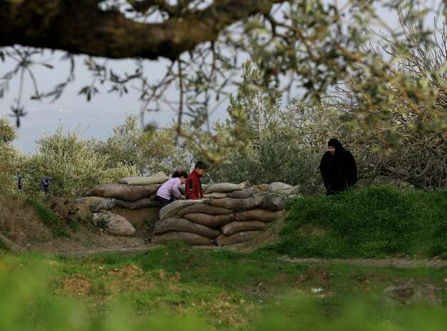 In this picture taken on Thursday, Syrian children, left, with their mother, right, check a sand bags barrier which was used as a battle position by the Syrian army government forces, at the Christian village of Jdeideh, in the northern Syrian province of Idlib, Syria. Syrian warplanes and artillery hit targets near Damascus International Airport on Friday following a particularly bloody day of attacks in the capital that killed dozens and struck deep into the heart of the city. Photo: AP