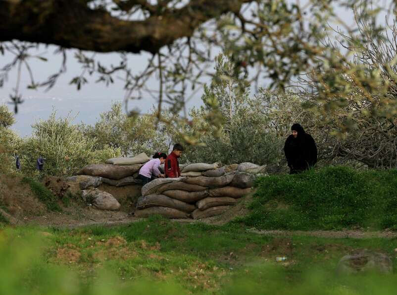 In this picture taken on Thursday, Syrian children, left, with their mother, right, check a sand bag