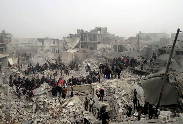 This citizen journalism image provided by Aleppo Media Center AMC, which has been authenticated based on its contents and other AP reporting, shows people searching through the debris of destroyed buildings in the aftermath of a strike by Syrian government forces, in the neighborhood of Jabal Bedro, Aleppo, Syria, Tuesday. The U.N. Commission of Inquiry on Syria released a 131-page report Monday, Feb. 18, 2013, detailing deepening radicalization by both sides and says fighters on both sides in Syria's civil war have committed atrocities and should be brought to justice. Photo: AP