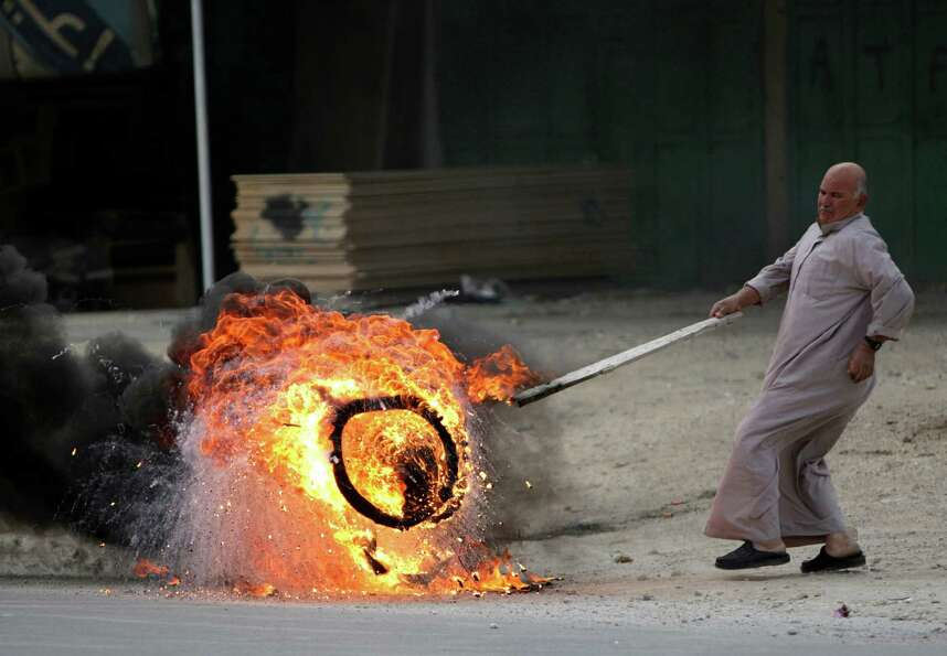A man pushes a burning tire in the West Bank town of Nablus during a rally in support of Palestinian