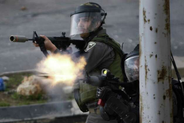 An Israeli border policeman fires with anti-riot ammunition towards Palestinian demonstrators, not pictured, during a protest to support Palestinian prisoners, outside Ofer, an Israeli military prison near the West Bank city of Ramallah, Tuesday. Palestinian protesters clashed with Israeli soldiers at a rally Tuesday in support of four imprisoned Palestinians on hunger strike, as hundreds of inmates said they were refusing food for the day in solidarity with the fasting inmates. One of the four hunger-striking Palestinians is 35-year-old Samer Issawi whose health has severely deteriorated after he has refused food, on-and-off, for more than 200 days. Photo: AP