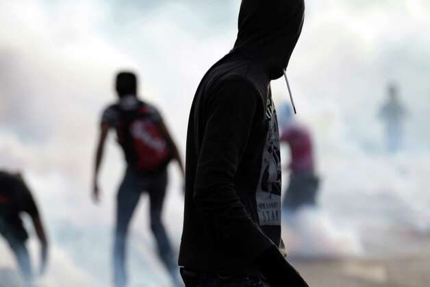 Bahraini anti-government protesters confront riot police, unseen, in a street filled with tear gas during clashes that erupted at a politically charged mourning procession in Daih, Bahrain, on Tuesday. Two Sunni factions in Bahrain say they are suspending participation in talks with Shiite opposition groups because of a spike in violence in the Gulf nation's two-year-old uprising. Photo: AP