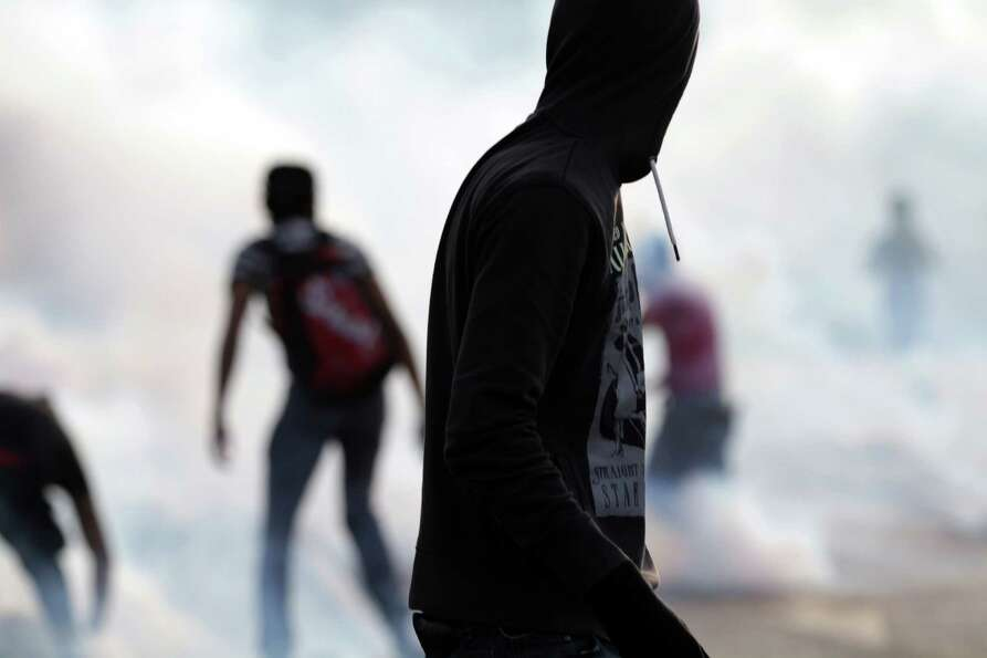 Bahraini anti-government protesters confront riot police, unseen, in a street filled with tear gas d