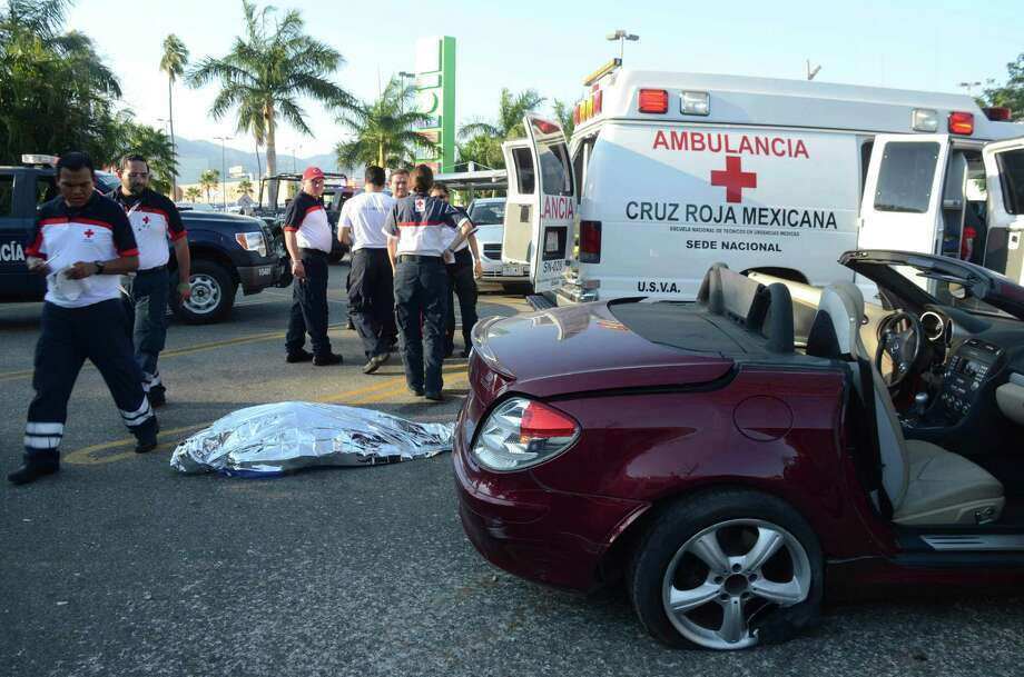 Emergency responders stand next to the body of a man identified as a Belgian citizen as he lies in the ground next to his car after he was shot dead by unknown assailants while he was leaving a supermarket in the Pacific resort city of Acapulco, Mexico, Saturday. The incident occurred a very short distance away from the Fairmont Acapulco Princess where the Mexico Tennis Open is slated to begin next Monday. Photo: AP