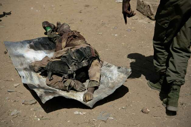 The body of an alleged jihadist is examined for grenades by Malian soldiers several days after militant Islamist rebels fought street battles with Malian and French forces, in Gao, Mali, on Saturday. The Chadian army said Saturday that its troops had killed 65 Islamic extremist rebels and destroyed five vehicles in the Adrar des Ifoghas mountains of northeastern Mali. According to the statement, 13 Chadian soldiers were also killed and six were wounded in the fighting Friday. Photo: AP