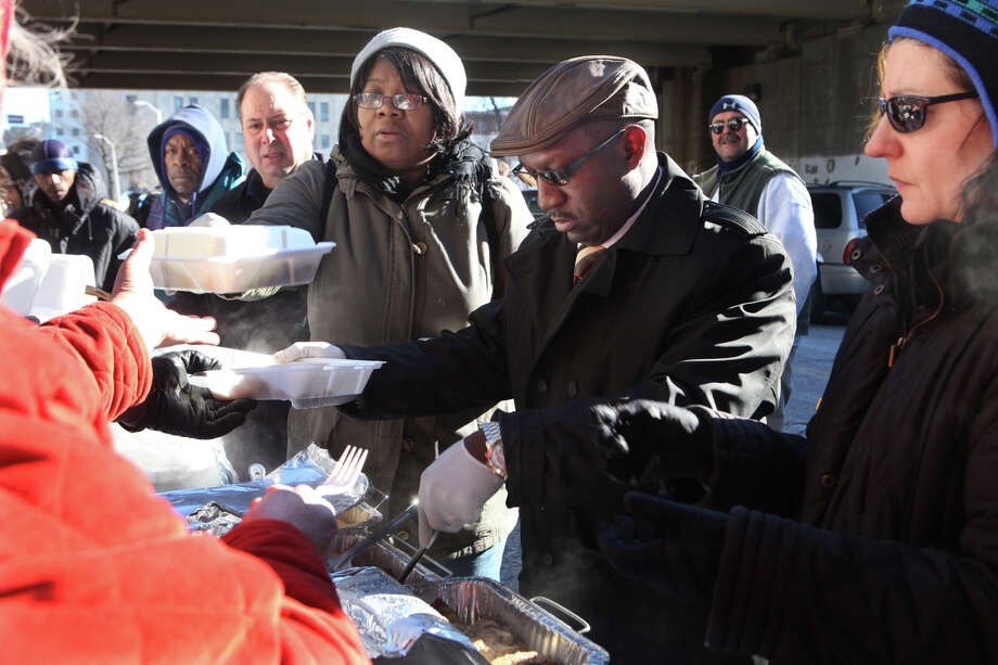 Volunteers, from left, Kenneth Anderson, Pastor G, Janet Short, Pastor Youngblood, and Michele Sommer, try to keep  Ann Marie Tarinelli's legacy of  feeding the needy and homeless on Sundays under the Rt. 25 overpass on John Street.  Tarinelli, of Trumbull, passed away in January. Photo: BK Angeletti, B.K. Angeletti / Connecticut Post freelance B.K. Angeletti