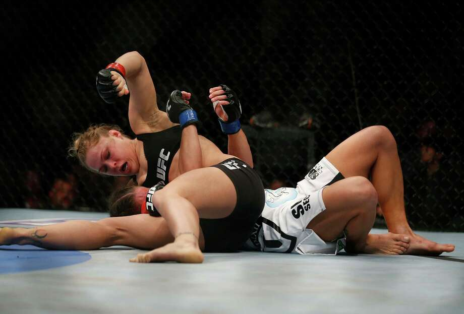 Ronda Rousey, top, punches Liz Carmouche during their UFC 157 women's bantamweight championship mixed martial arts match in Anaheim, Calif., Saturday, Feb. 23, 2013. Rousey won by tapout in the first round. (AP Photo/Jae C. Hong) Photo: Jae C. Hong, Associated Press / AP