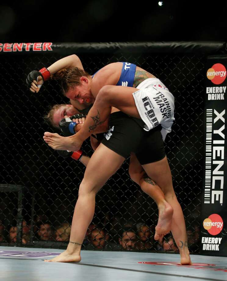 Ronda Rousey, bottom, and Liz Carmouche fight during their UFC 157 women's bantamweight championship mixed martial arts match in Anaheim, Calif., Saturday, Feb. 23, 2013. Rousey won by tapout in the first round. (AP Photo/Jae C. Hong) Photo: Jae C. Hong, Associated Press / AP