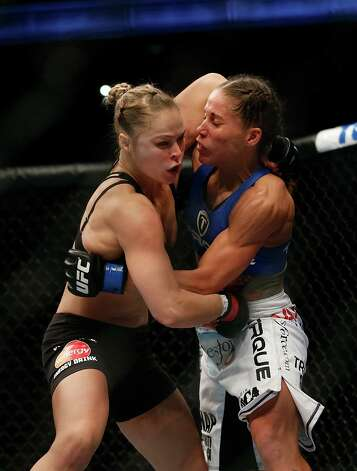 Ronda Rousey, left, fights Liz Carmouche during their UFC 157 women's bantamweight championship mixed martial arts match in Anaheim, Calif., Saturday, Feb. 23, 2013. Rousey won by tapout in the first round. (AP Photo/Jae C. Hong) Photo: Jae C. Hong, Associated Press / AP
