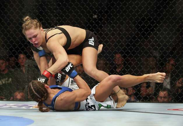 Rousey (7-0) defended her belt with her seemingly inevitable move, forcing Carmouche to tap out after bending back her arm. Rousey raised both arms in victory while flat on the canvas after the longest fight of the mixed martial artist's ascendant career. Photo: Jeff Gross, Getty Images / 2013 Getty Images