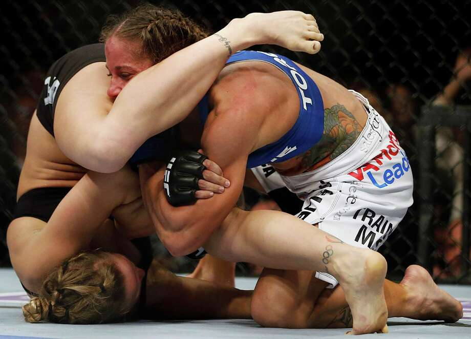 Ronda Rousey, left, tries to pull an armbar on Liz Carmouche during their UFC 157 women's bantamweight championship mixed martial arts match in Anaheim, Calif., Saturday, Feb. 23, 2013. Rousey won the first women's bout in UFC history, forcing Carmouche to tap out in the first round. (AP Photo/Jae C. Hong) Photo: Jae C. Hong, Associated Press / AP