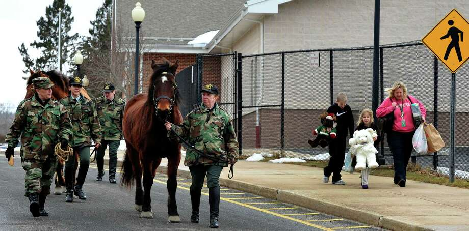 Members of the Second Company Governors Horse Guard walk outside Reed Intermediate School in Newtown, Conn. as parents and children from Sandy Hook leave with donated goods Sunday, Feb. 24, 2013. Photo: Michael Duffy / The News-Times