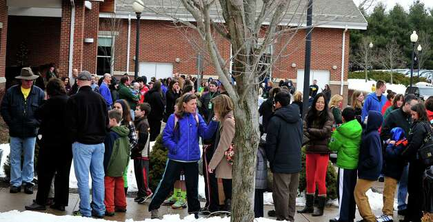 Parents and children from Sandy Hook wait outside Reed Intermediate School in Newtown, Conn. for a give away of donated goods Sunday, Feb. 24, 2013. Photo: Michael Duffy / The News-Times