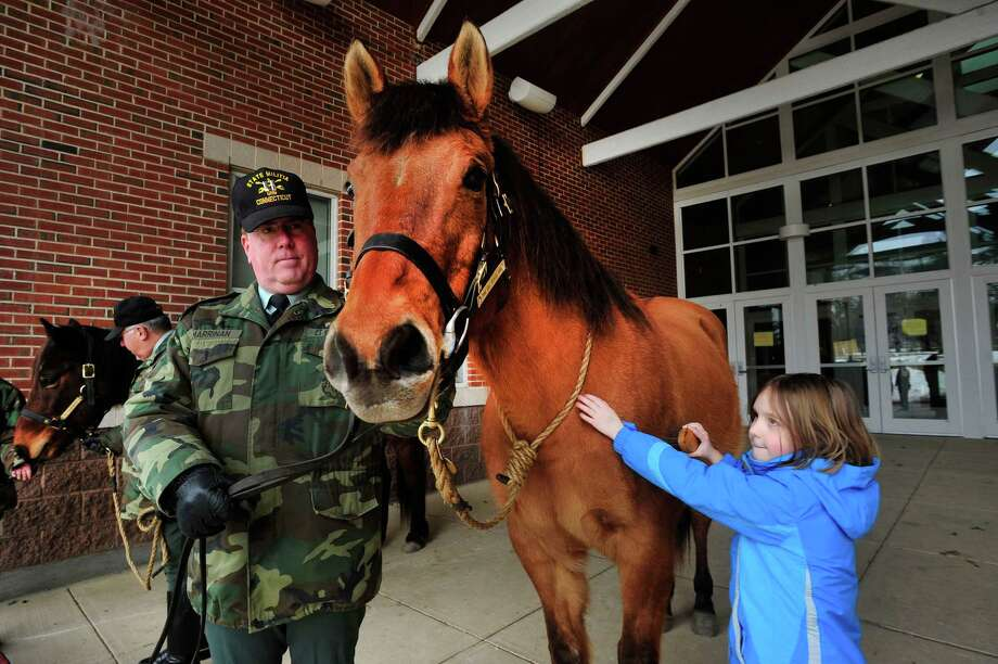 Treasa O'Sullivan, 8, pets Casino, held by Capt. James Marrinan, of the Second Company Governors Horse Guard. The Horse Guard was outside Reed Intermediate School in Newtown, Conn. as parents and children from Sandy Hook wait for a give away of donated goods Sunday, Feb. 24, 2013. Photo: Michael Duffy / The News-Times