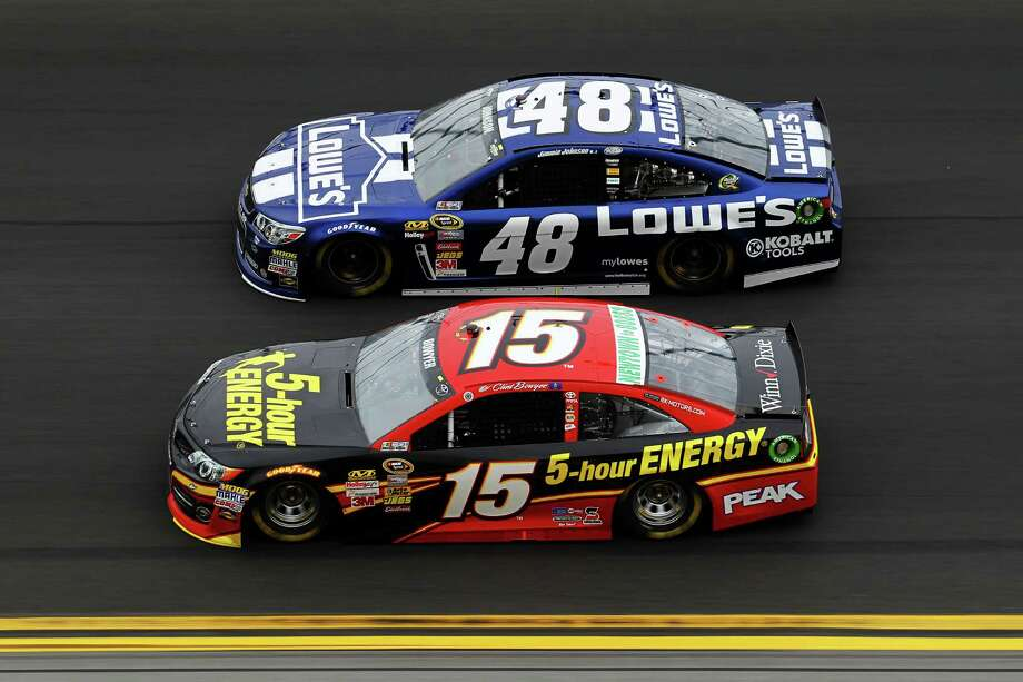 Clint Bowyer, driver of the #15 5-hour ENERGY Toyota, and Jimmie Johnson, driver of the #48 Lowe's Chevrolet, race  during the NASCAR Sprint Cup Series Daytona 500. Photo: Todd Warshaw, Getty Images / 2013 Getty Images